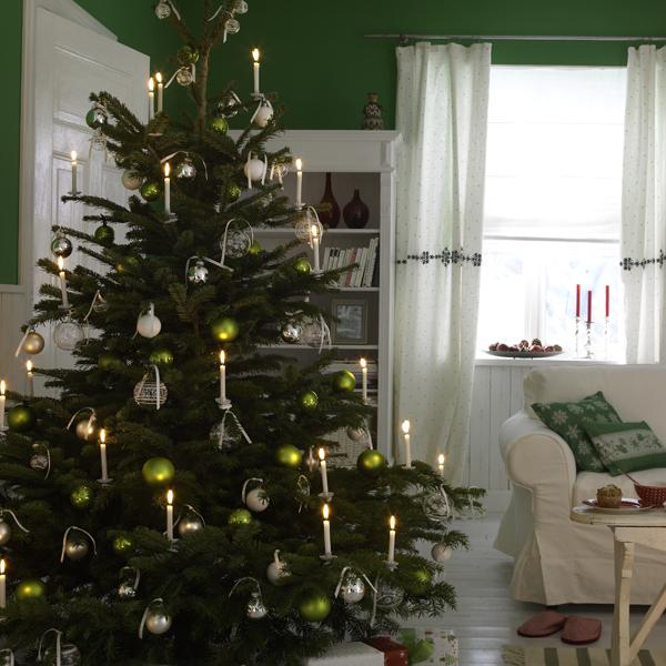 Edler Weihnachtsbaum. Prächtig in Grün, Silber und Weiß herausgeputzt, steht der deckenhohe Christbaum im Mittelpunkt ? auch später, wenn die Geschenke an seinem Fuß schon ausgepackt sind